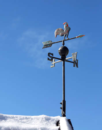 cardinal points: weathervane and blue sky on the roof with snow in winter