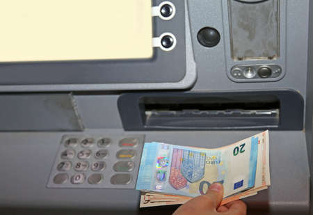 bankomat: boy who withdraws money from an ATM machine in euro banknotes in europe Stock Photo