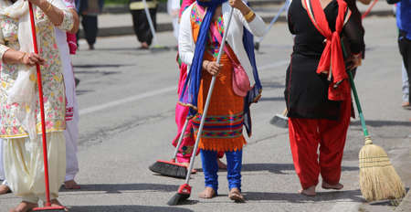 kameez: Sikh women while scavenging the street with a broom during a Sikh festival
