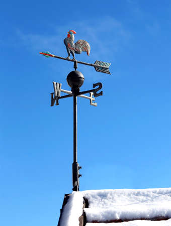 weathervane and blue sky on the roof with snow Фото со стока