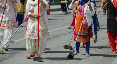 many Sikhs  women barefoot while scavenging the road during a Sikh festival