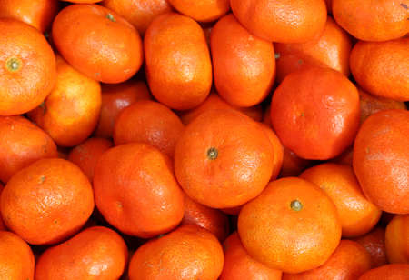 clementines: ripe orange background of many clementines for sale at the greengrocer Stock Photo