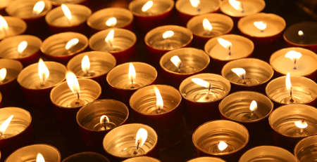 many candles lit with the warm flame during the religious ceremony
