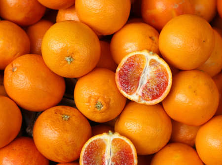ripe Oranges and slices of an orange cut in the greengrocers stall Stock Photo