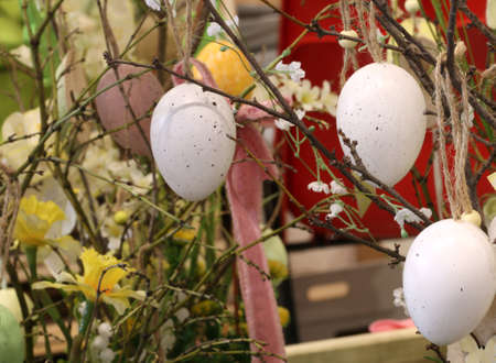 chicken egg hanging from a peach branch to decorate the house during the Easter celebrations Stock Photo