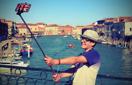 teenage boy smiles while he takes a picture by his smartphone near Venice in Italy