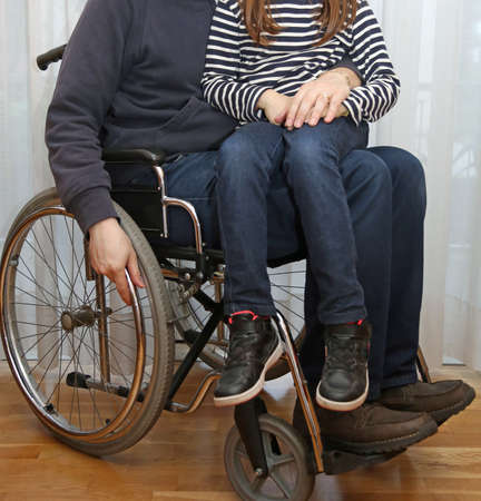 young disabled parent in a wheelchair with his young daughter