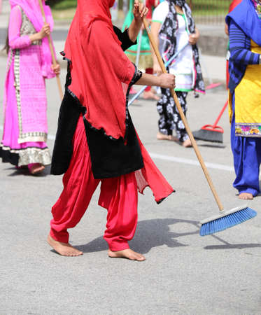 kameez: many Sikh  women barefoot while scavenging the road with a broom during a Sikh festival Stock Photo