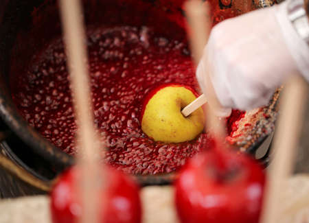Cook hand with the glove and red apple with caramelized sugar syrup Stock Photo