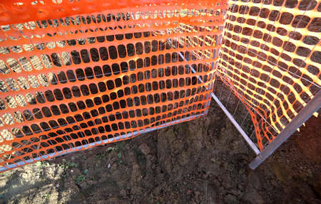 trenching: Orange safety net in a road construction site in the city