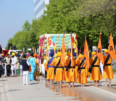 Vicenza, VI, Italy - April 8, 2017: barefooted men with turbans and scimitars and orange flag at the ceremony of the Sikh religion Editorial