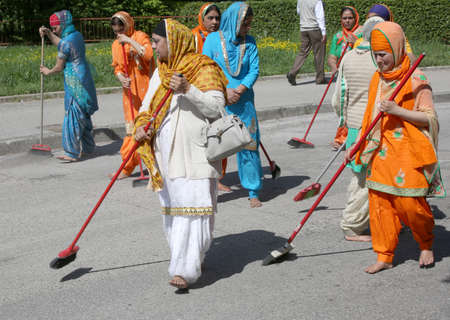 Vicenza, Vi, Italy - April 8, 2017: Sikh religious  barefoot women sweeping the street with brooms during the Nagar Kirtan festival