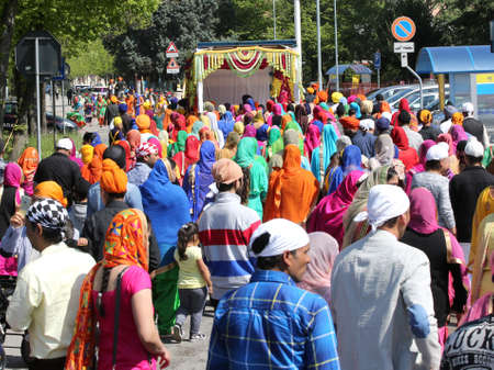 punjab: Vicenza, VI, Italy - April 8, 2017: many people Sikh religious procession pray during a ceremony Nagar Kirtan on the street