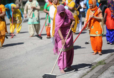 cleaning service: Vicenza, Vi, Italy - April 8, 2017: Sikh religious  barefoot women sweeping the street with brooms during the Nagar Kirtan festival