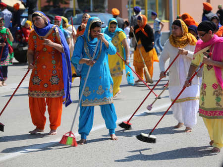 Vicenza, Vi, Italy - April 8, 2017: barefoot women Sikh religious ceremony sweep the street with brooms during the Nagar Kirtan festival