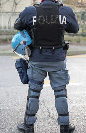 Italian policeman in riot gear with helmets and batons before a football match