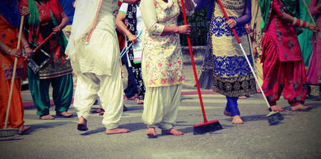 kameez: Sikh women with a broom while scavenging the street during a Sikh festival