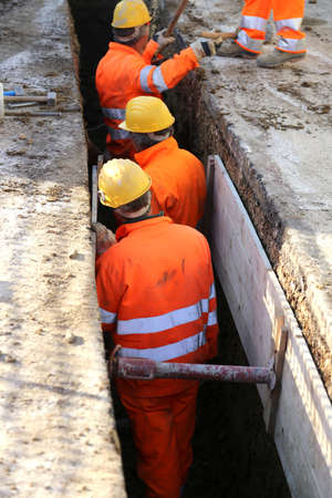 trenching: men at work with yellow helmet inside the trench of road construction site