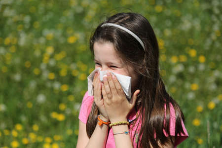 Young girl with long brown hair with allergy to the grasses blows her nose with the handkerchief Stock Photo