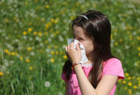 Little Child with brown hair with allergy to the grasses blows her nose with the handkerchief in spring