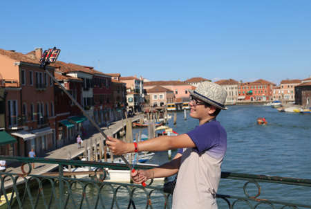 selfy: young teenage boy smiles while he takes a picture by his smartphone on the bridge of the island near Venice in Italy Stock Photo