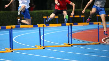 Hürdenlauf, drei Jungs springen über Hürden auf einer Laufbahn