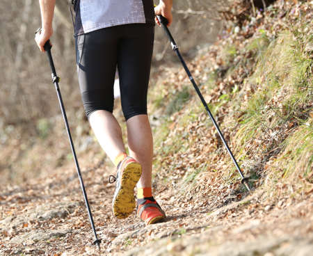 crosscountry: Young runner runs in the mountains with nordic walking sticks