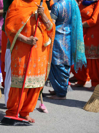 kameez: Barefoot women with traditional clothes sweep the way during the sikh religion ceremony Stock Photo
