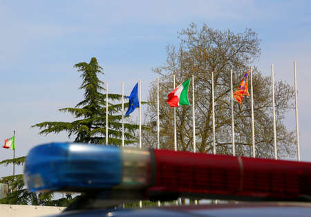 Police car sirens with blurry effect and European and Italian flags in background Stock Photo