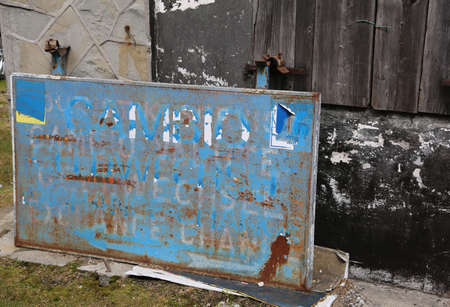 Old abandoned billboard of a change money office  at a border between European states before using the Euro coin Imagens - 77415937