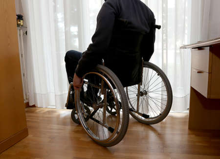 disabled person in his bedroom with a desk and closet