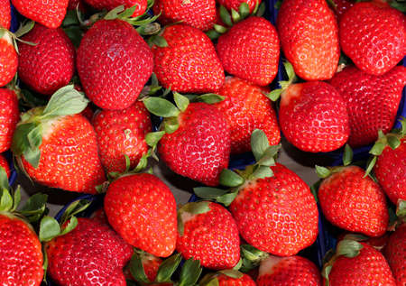 background of ripe red strawberries for sale at the greengrocer