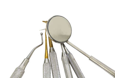 Many dental tools for cleaning the teeth and checking the caries with the round little mirror on white background