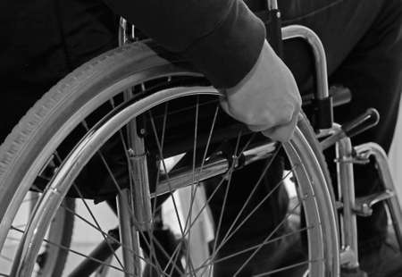 detail of the wheelchair with the hand of the disabled person on the wheel with black and white effect Stock Photo