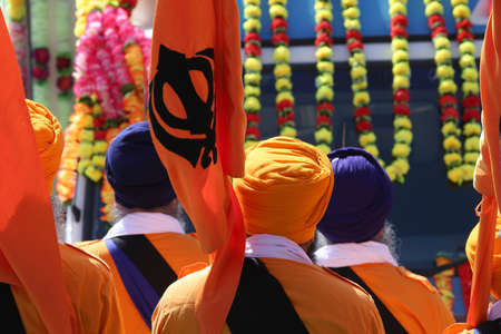 Sikh religion people with orange flags and dresses during the religious ceremony