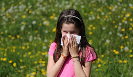 Young girl with long brown hair with allergy to the pollen blows her nose with the handkerchief in the middle of the meadow Stock Photo