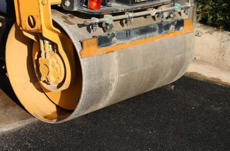 detail of an heavy road roller with the black asphalt of a street