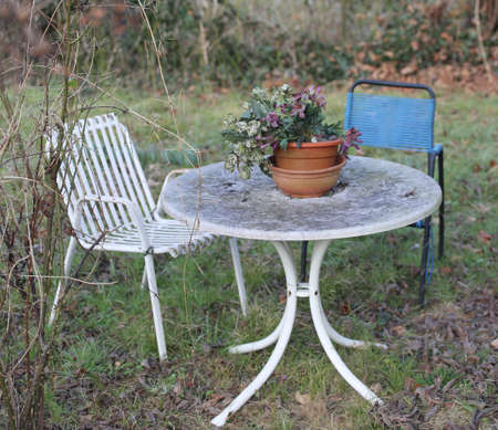 abbandoned garden with chairs and a old little table