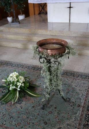 Antigua fuente bautismal pequeña en cobre decorada con flores durante la celebración religiosa dentro de la iglesia