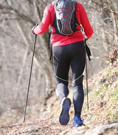 Man runs on the mountain path with nordic walking poles and backpack