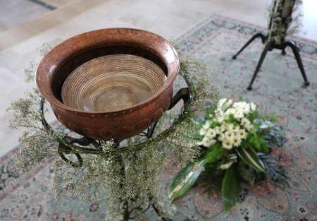 Antiguo Pequeña fuente bautismal en cobre decorada con flores durante la celebración religiosa