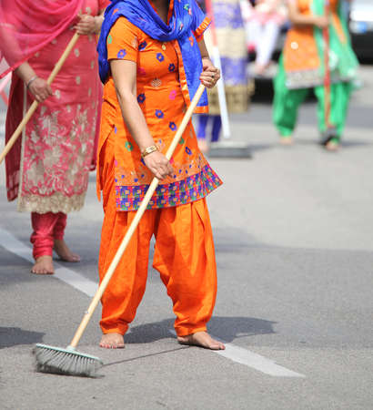 Sikh women with a broom while scavenging the street during a Sikh festival
