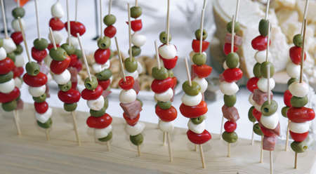 tasty skewers of tomatoes mozzarella and green olives and baloney