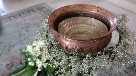 Ancienne petite fonts baptismale en cuivre pendant la célébration religieuse à l'intérieur de l'église Banque d'images - 78237155