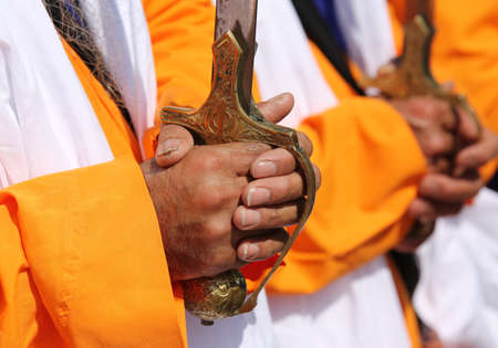 hand of a sikh man on the hilt of the sword