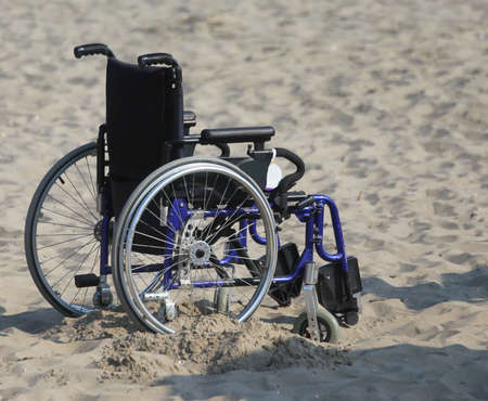 Wheelchair with wheels locked in the sand of the beach in summer