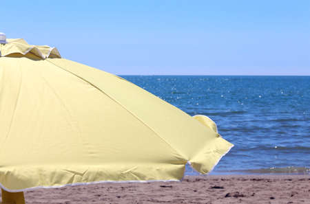 Large yellow sun umbrella on the shore of the ocean in the hot sunny day Stock Photo