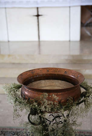 baptismal font in copper during the religious celebration inside the church