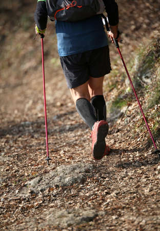 Man practices nordic walking sport on the mountain trail with nordic walking poles Фото со стока