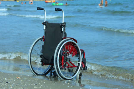 Wheelchair on the shore by the sea on a sunny summer day Stock Photo